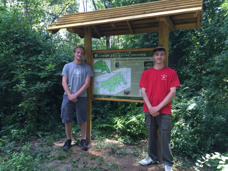 Boy Scout Chris Bell (on right in red) and fellow Scout Douglas Connell (on left in grey), in front of new informational kiosk Chris designed and built as part of his Eagle Scout project.